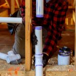 Plumber installing primer and glue PVC pipe